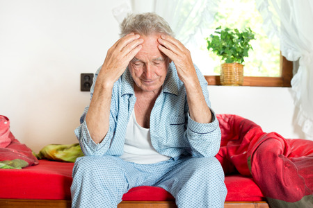 27897788 - old man sitting on bed and holding head with hands