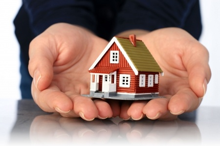 7023687 - hands and small house. real estate or insurance concept.