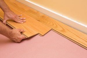 43696536 - series of shots of engineered hardwood floor being installed by a worker over pink felt paper using hand tools